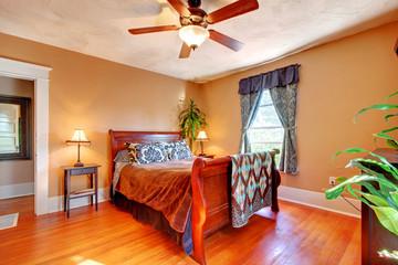 Bedroom with Brown walls with cherry hardwood floor.