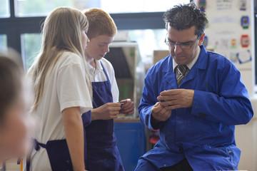 Teacher and students in school workshop