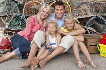 Portrait of smiling family leaning against lobster traps