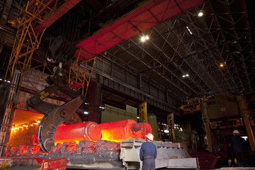 Engineers watching molten forged steel in furnace