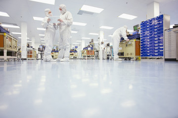 Scientists in clean suits talking in silicon wafer manufacturing laboratory