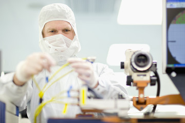 Scientist in clean suit adjusting wires on machine in silicon wafer manufacturing laboratory