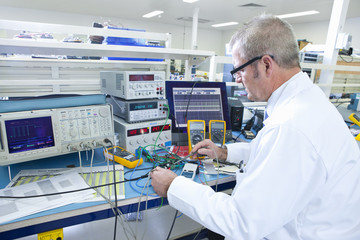 Engineer working at electrical test bench next to oscilloscope