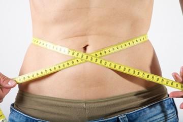 slim female measuring her waist