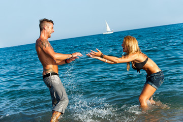 Attractive girl splashing her boyfriend on beach.