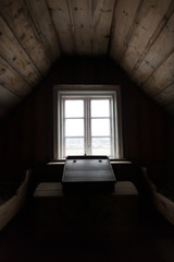 Dark wooden attic room with desk by window