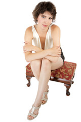 Classy fashionable young woman seated on low footstool.