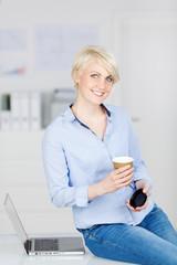 lachende geschäftsfrau mit einem becher kaffee