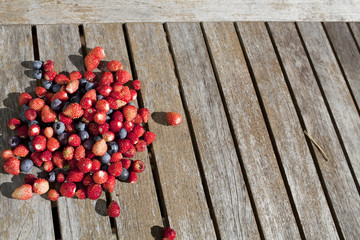 wild strawberry and bilberry  are on the wooden table