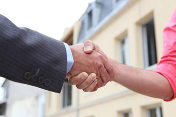 Couple shaking hands outside a house