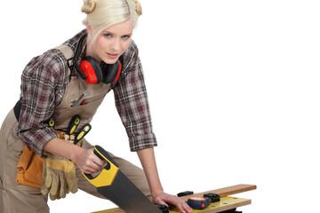 A female carpenter sawing.