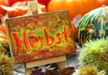 Herbstschild mit Kastanien und Kürbissen