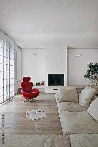 poltrona rossa e camino nel soggiorno moderno\