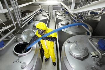 technician in uniform filling large  silver tank in factory