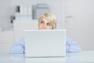 junge frau schaut nachdenklich über ihren laptop
