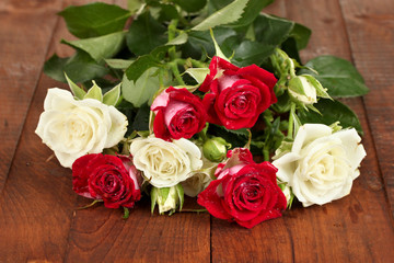 Bouquet of beautiful roses on wooden background close-up