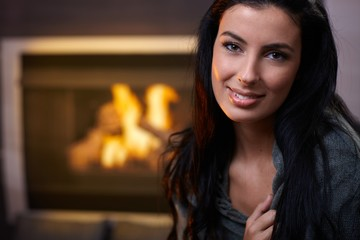 Beautiful woman by fireplace