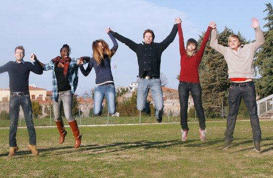 studenti multietnici saltano per mano allegramente