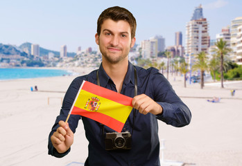 Portrait of a young man holding a flag
