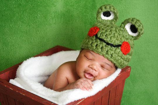 Smiling newborn baby boy wearing a green crocheted frog hat