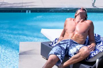 Fit Man Sunbatheing by Pool