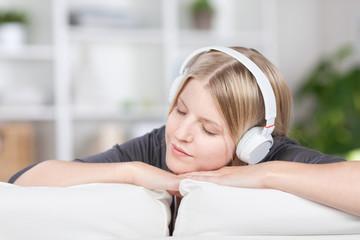 frau hört musik auf dem sofa