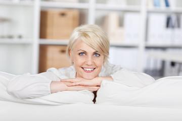 lächelnde frau stützt den kopf auf das sofa
