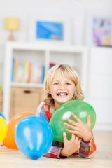 lachendes kleines mädchen liegt zwischen luftballons