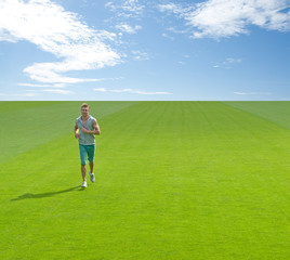 Sporty young man running on green field