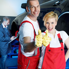 Two car mechanics in garage show thumbs up