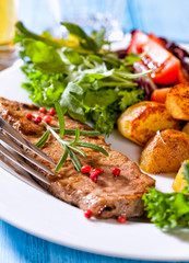 Grilled steak with baked potatoes and salad