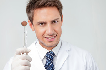 Dentist Holding Angled Mirror And Carver