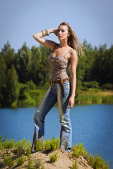 Cowgirl in jeans stands on the bank of forest river