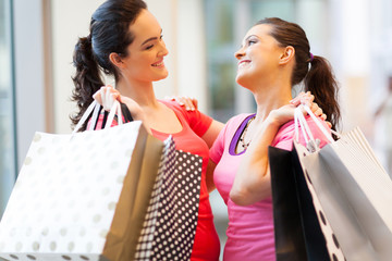happy friends shopping in mall