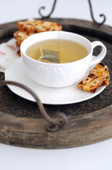 White cup of green tea and biscotti on wooden tray