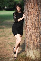 Ragazza  con vestito nero appoggiata all'albero