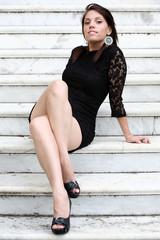 Ragazza con vestito nero sulla scala di marmo