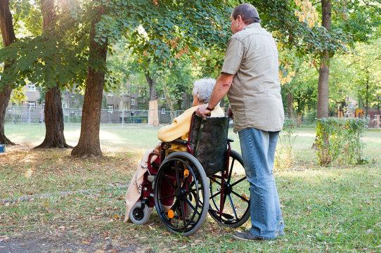Rollstuhlfahrerin mit Betreuer im Park