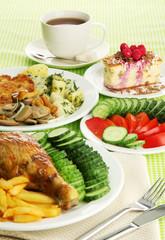Roast chicken with french fries and  vegetables, cup of tea and