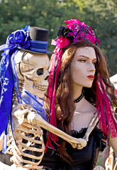 Fancy dressed female mannequin lovingly holding a skeleton.
