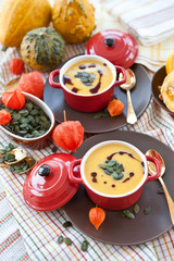 Zwei kleine rote Töpfe mit Deckel mit Kürbissuppe, Kürbiskernen