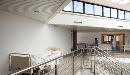 Patient lying in bed in corridor