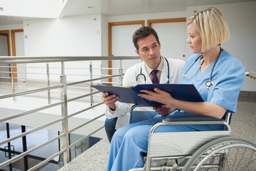 Doctor and nurse in wheelchair studying folder