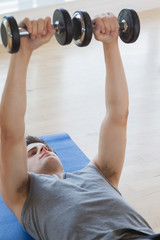 Man lifiting dumbbells while lying