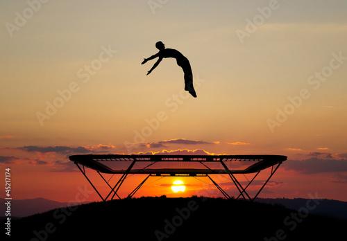 Fototapete gymnast on trampoline in sunset