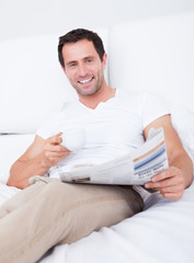 Young Man Holding Cup In Hand Reading Newspaper