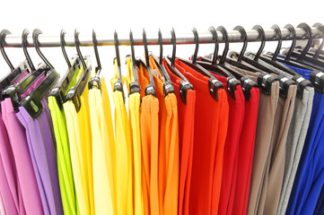 A row of colorful female trousers on hangers