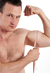Strong man measuring his bicep muscle. Isolated on white backgro