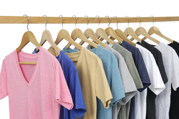 Row of different colors shirts on wooden hangers