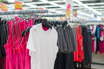Bright t-shirts and shorts on stands in supermarket